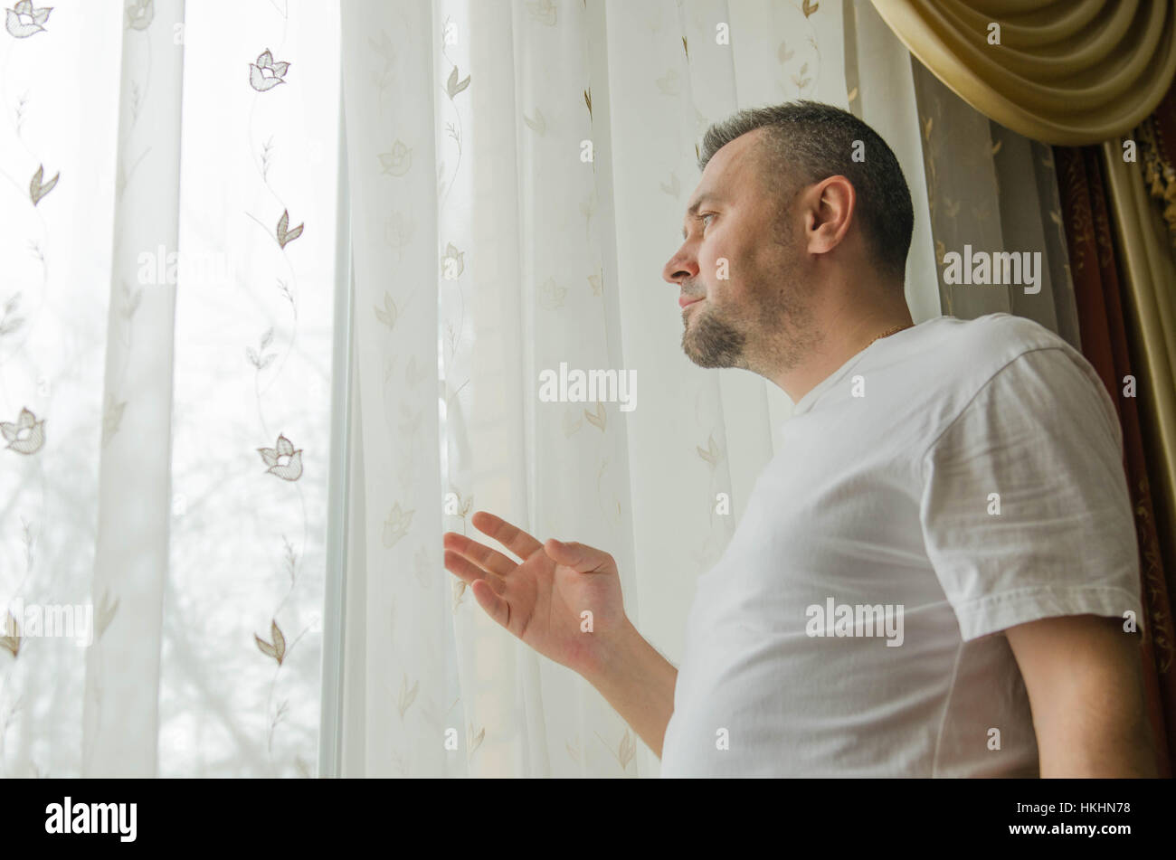 young man looking through a window blind - Stock Image