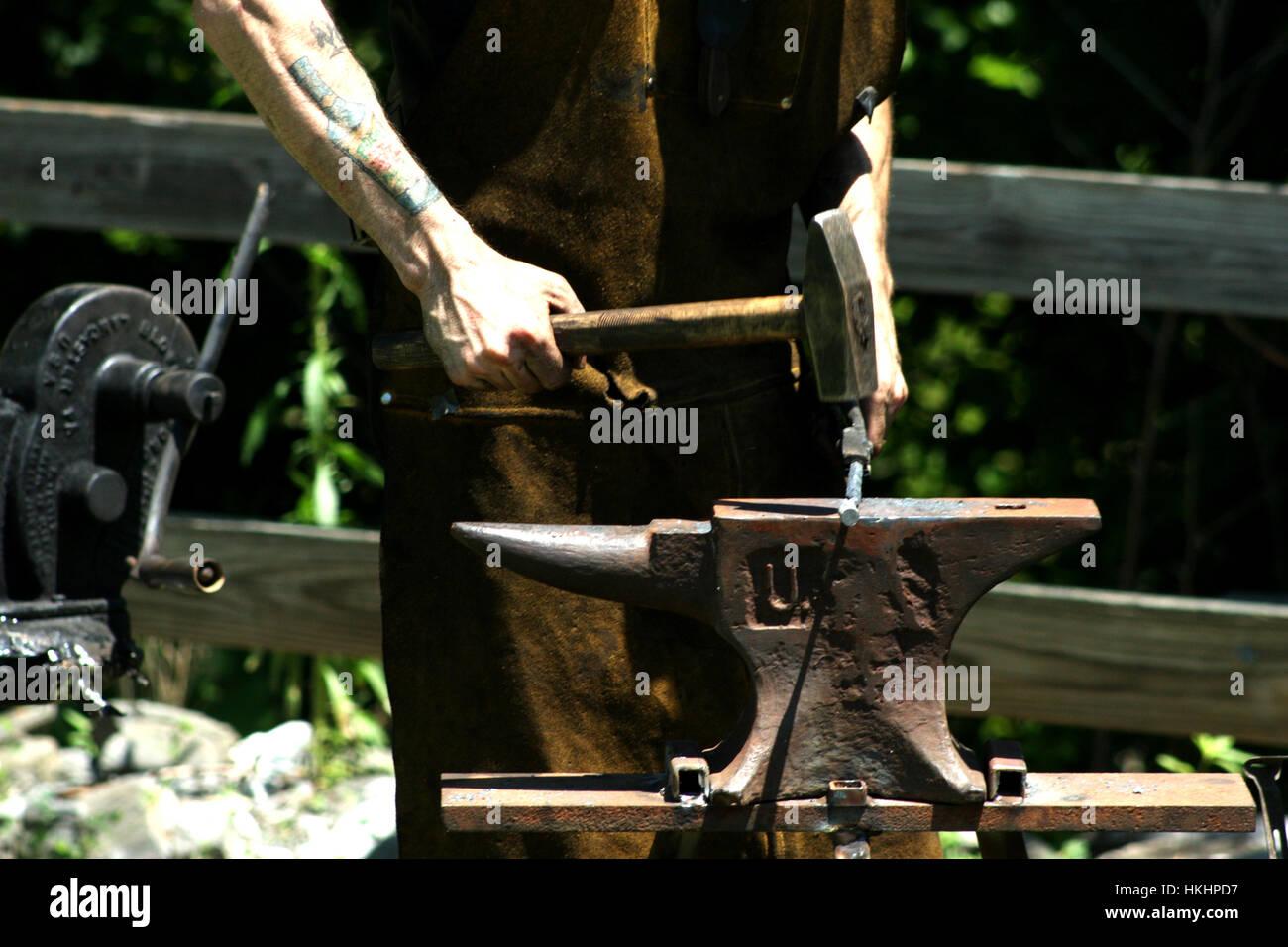 Blacksmith manually forging the molten metal on the anvil Stock