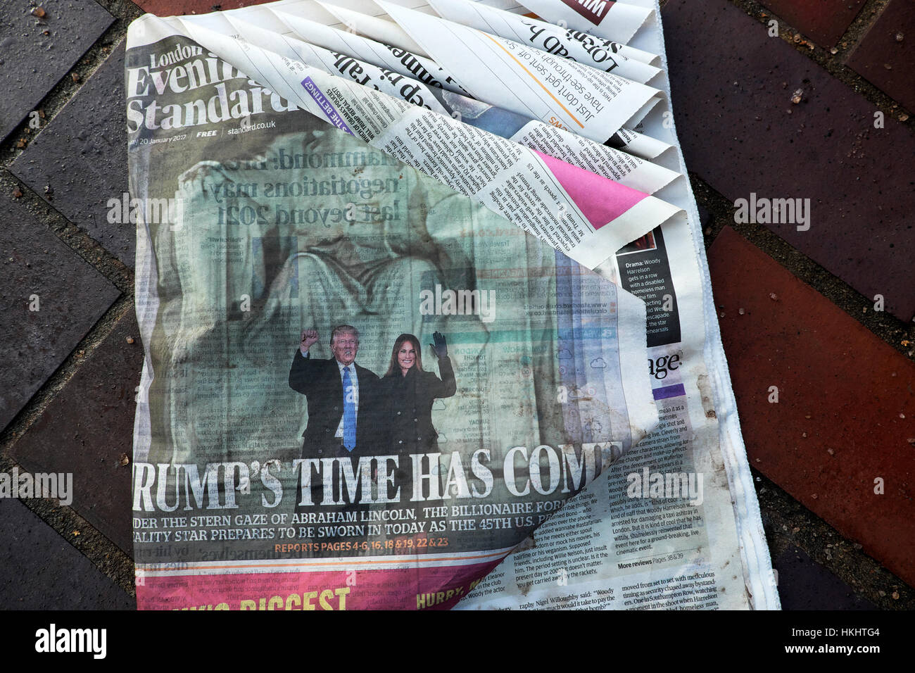 An old wet Sunday newspaper lies on the pavement in London after Donald Trump's inauguration ceremony in January - Stock Image