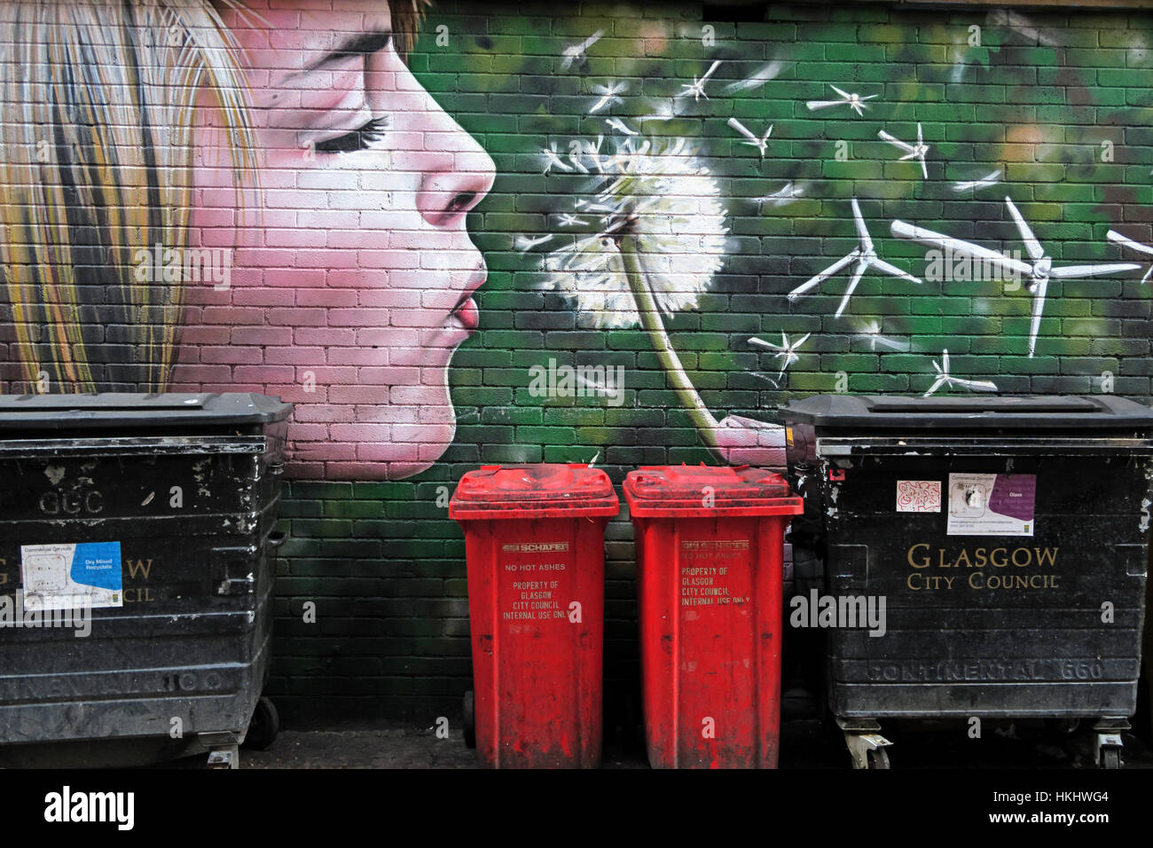 Girl blowing flower, Glasgow - Stock Image