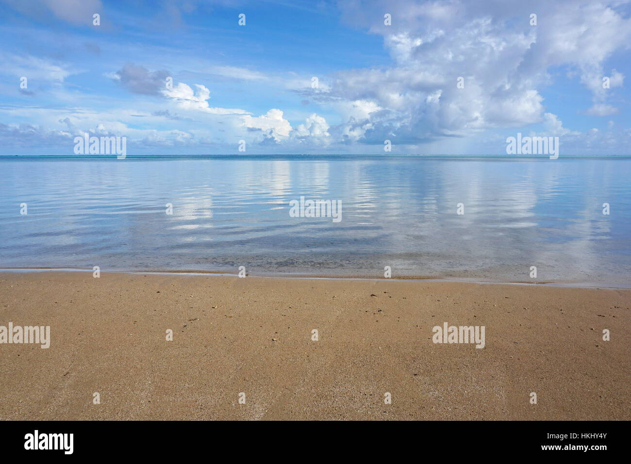 Peaceful seascape horizon with beach sand in foreground and calm water surface of the lagoon of Huahine island, - Stock Image