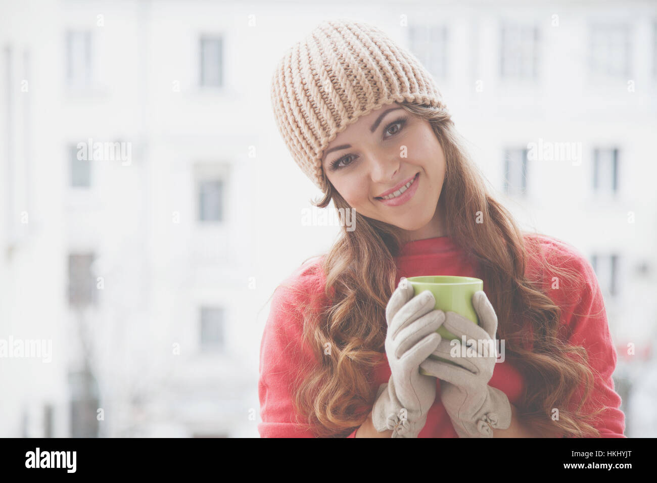 c9b9bb471 beautiful girl in a hat and gloves, drinking hot tea Stock Photo ...