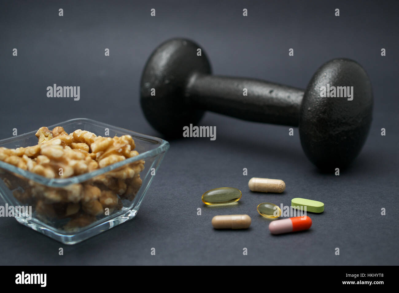 Dumbbell, walnuts and dietary supplements on dark background: fitness and muscle building concept. - Stock Image