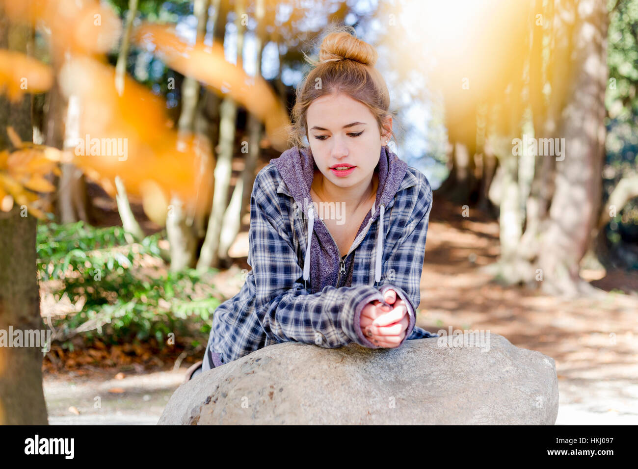 This young teenage girl hangs out alone in a park, sitting on a rock in a thoughtful disengaged position thinking - Stock Image