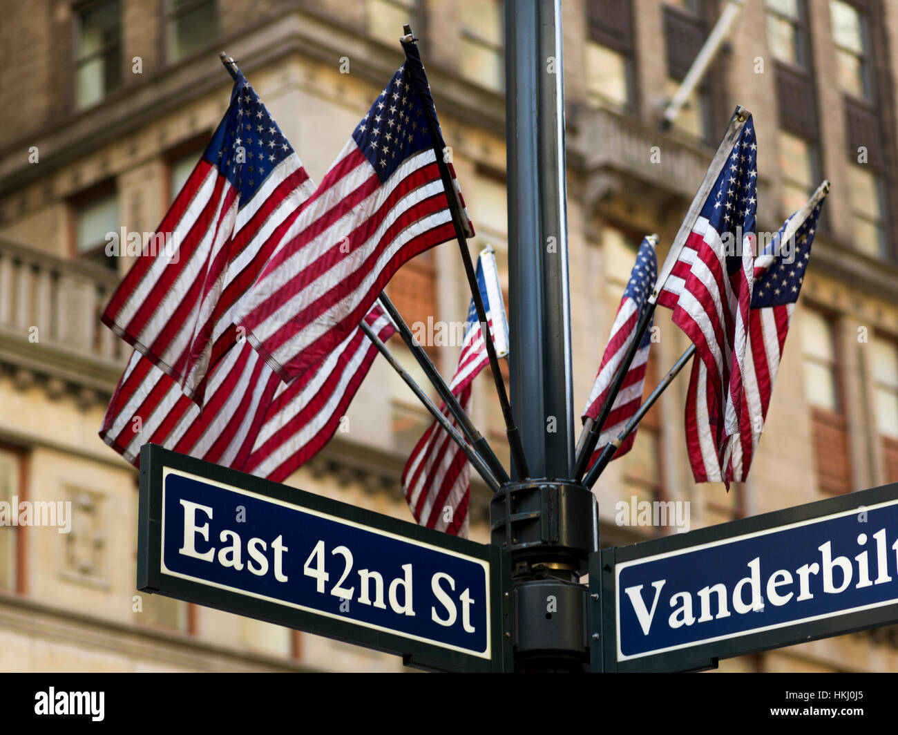 American flags on a pole above the street signs at the intersection of East 42nd Street and Vanderbilt - Stock Image
