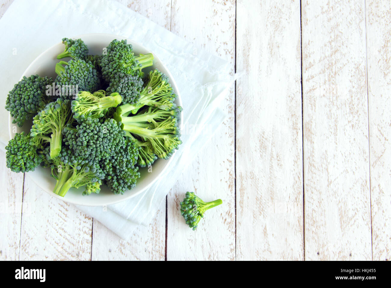 Healthy green organic raw uncooked broccoli on white wooden table with copy space - Stock Image