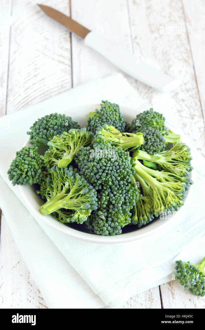 Healthy green organic raw broccoli on wooden table close up - Stock Image