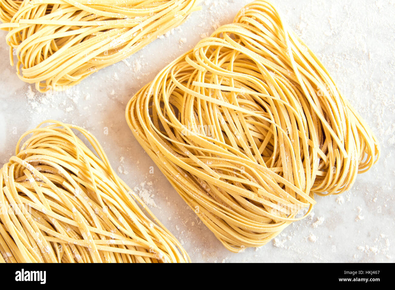 Homemade Raw Egg Noodles on a white background close up - Stock Image