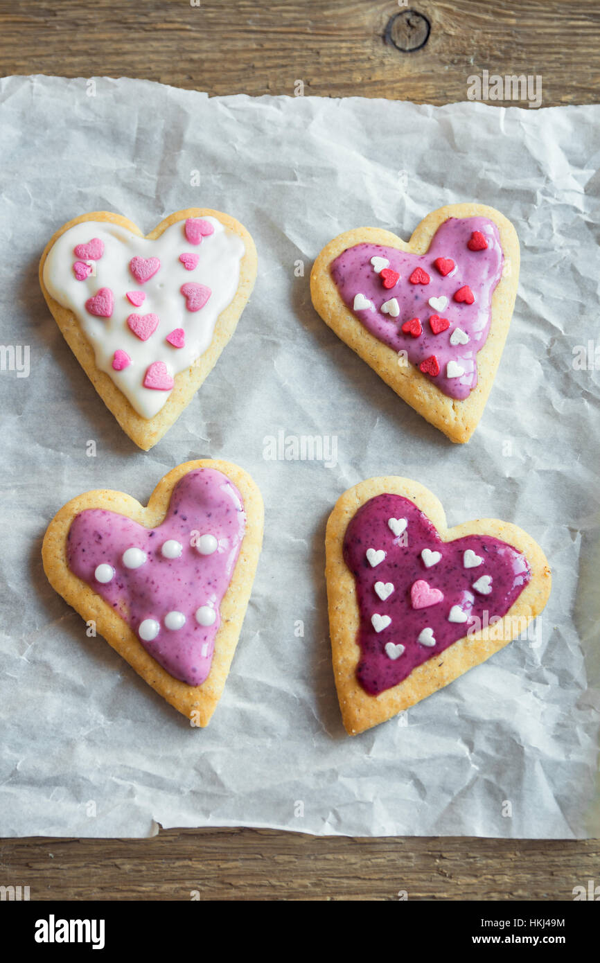 Heart shaped cookies close up for Valentine day - homemade festive decorated pastry buiscuits cookies on baking - Stock Image