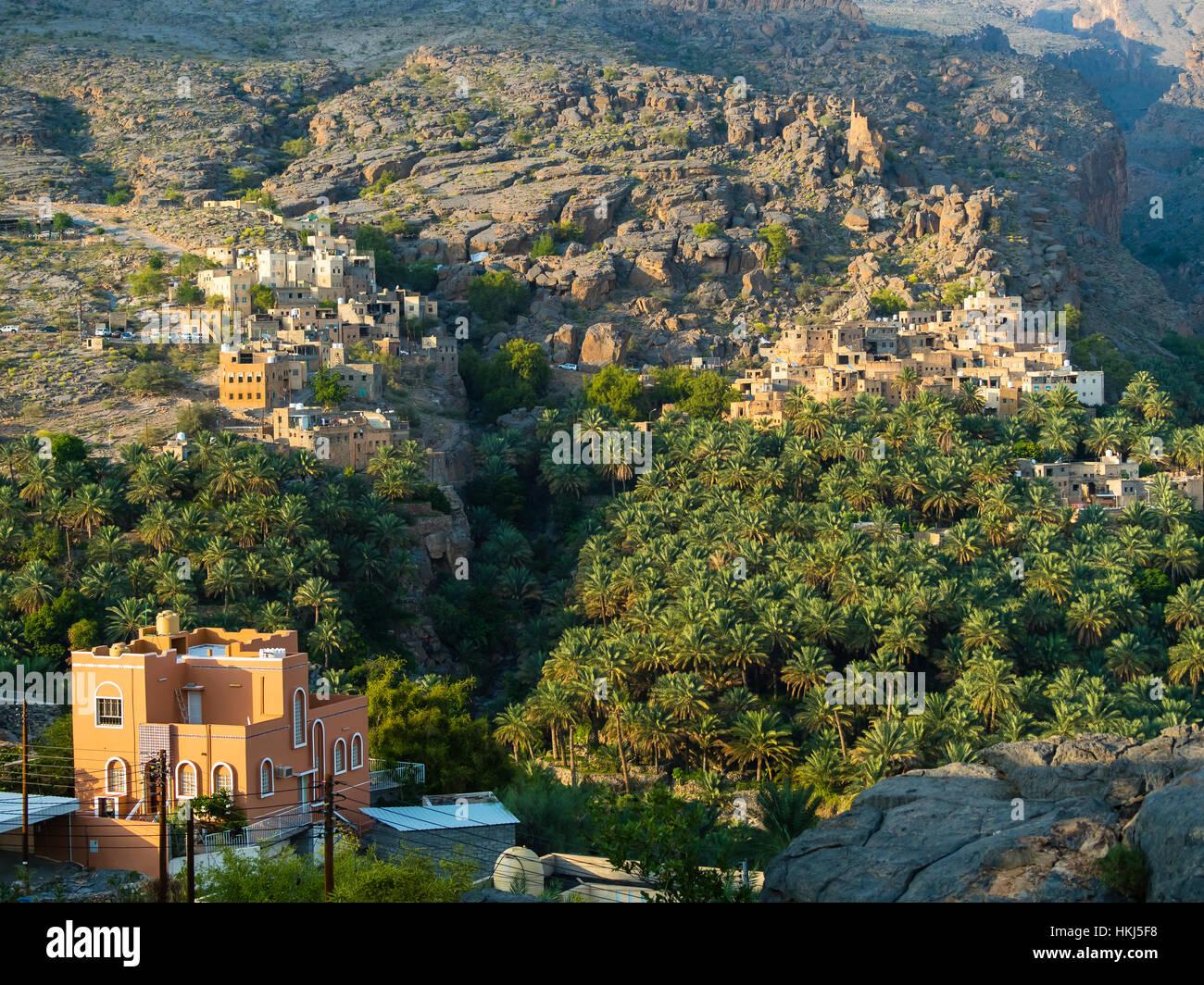 Oasis Al-Hamra with mountain village Misfah Wadi, Jebel Shams, Al Hajar Mountains, Dhakiliya Region, Oman - Stock Image