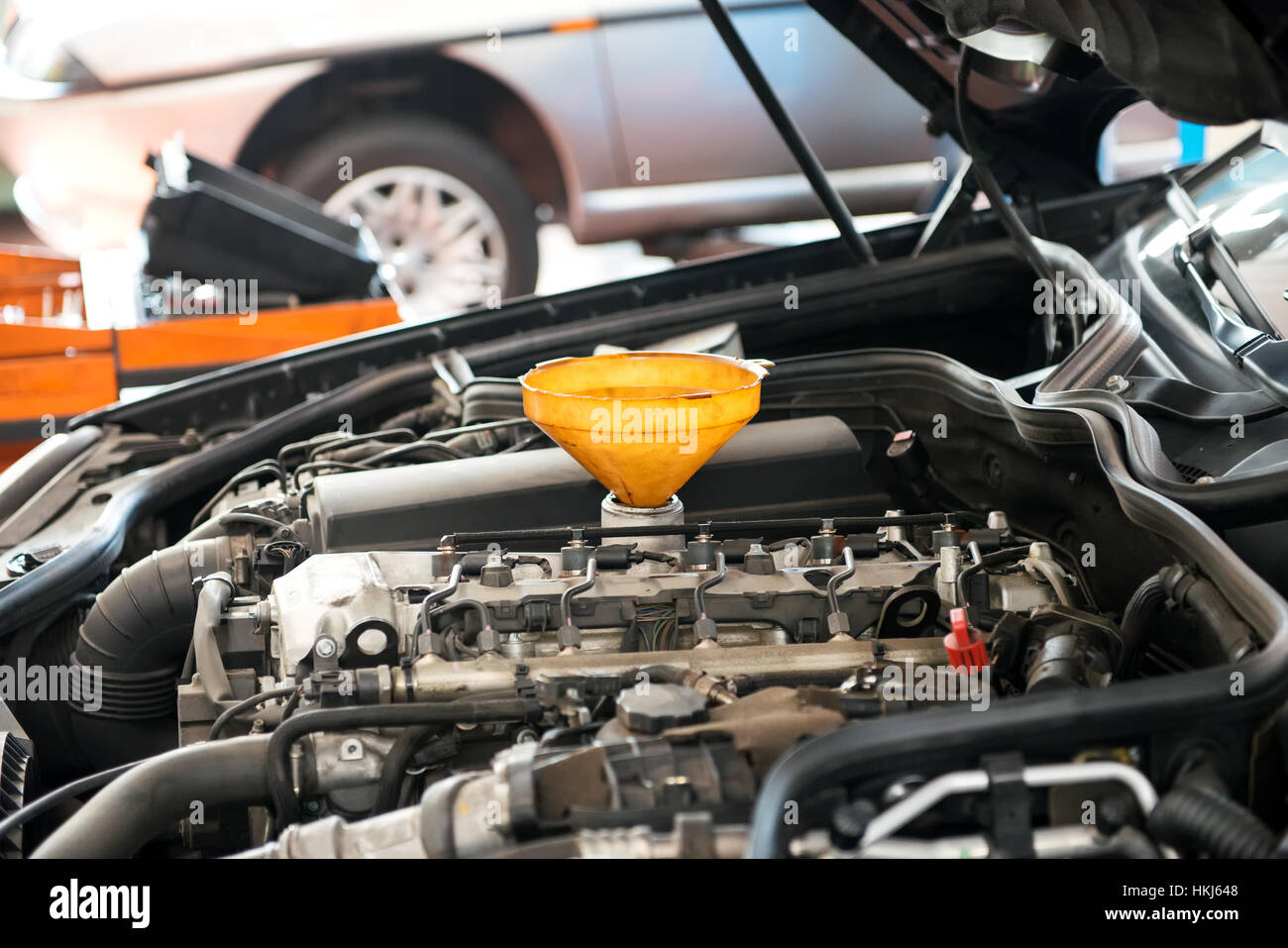 Close-up side view of car engine under opened hood with funnel inserted for oil pouring maintenance - Stock Image