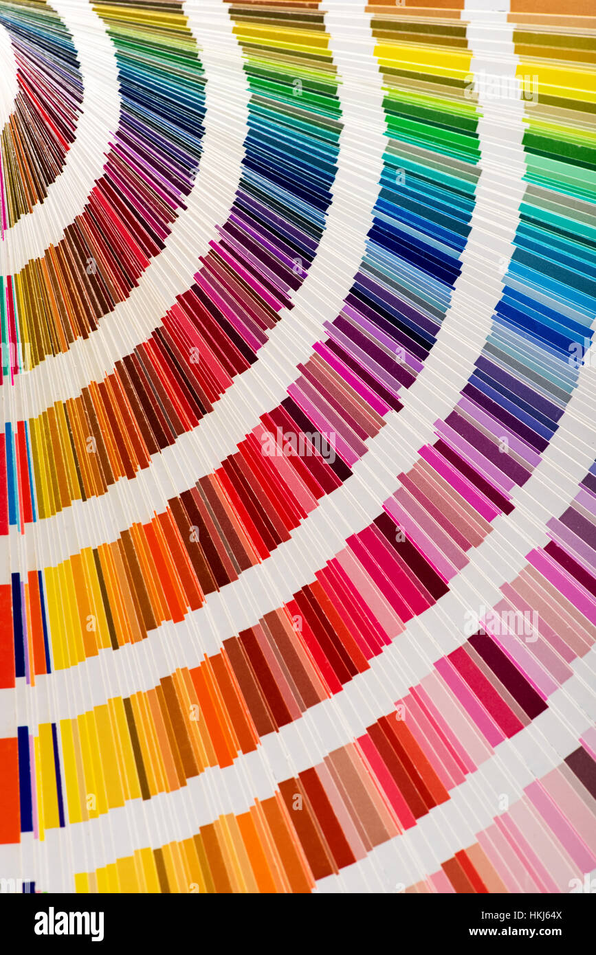 Close-up of color fan deck sampler with great variety of vivid colors forming rainbows. Background concept - Stock Image