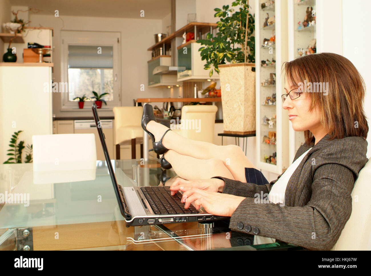Young business woman using laptop at home - Stock Image