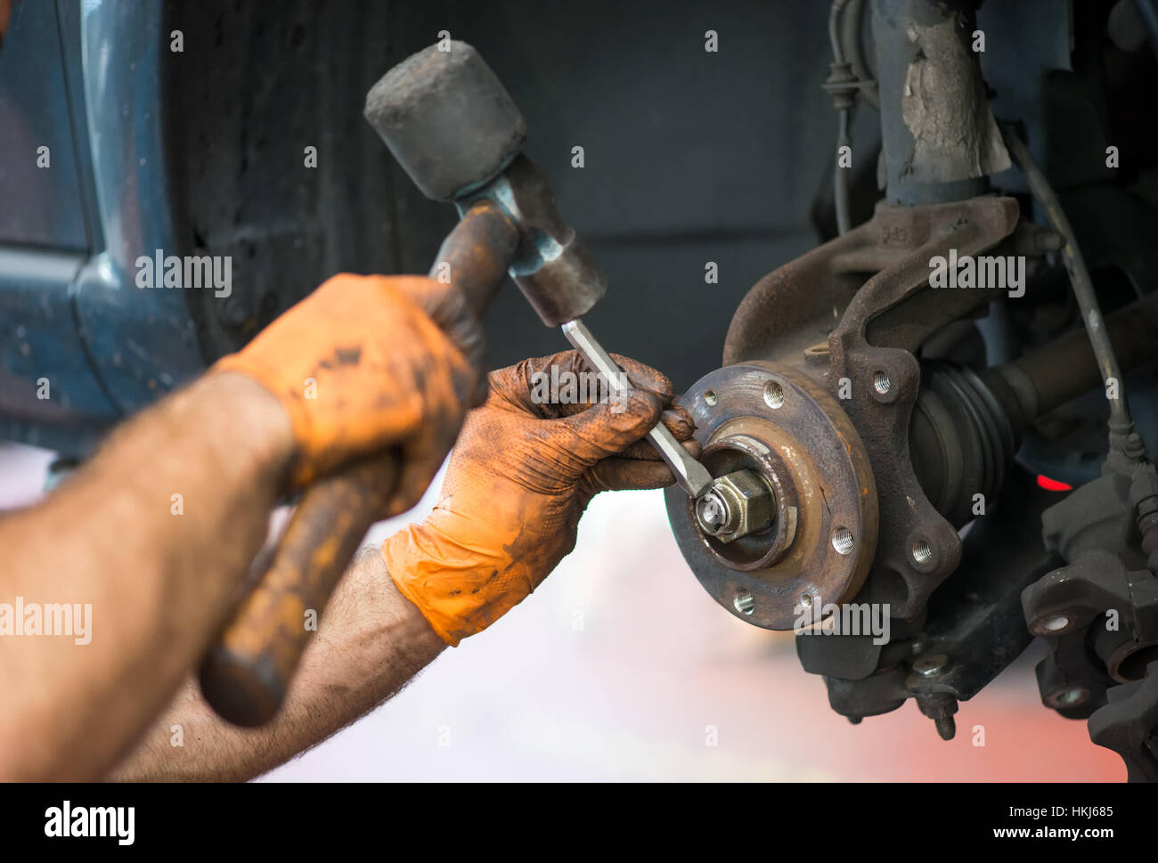 Close up view of incognito mechanic hands in dirty orange gloves trying to unscrew the nut with hammer of wheel - Stock Image