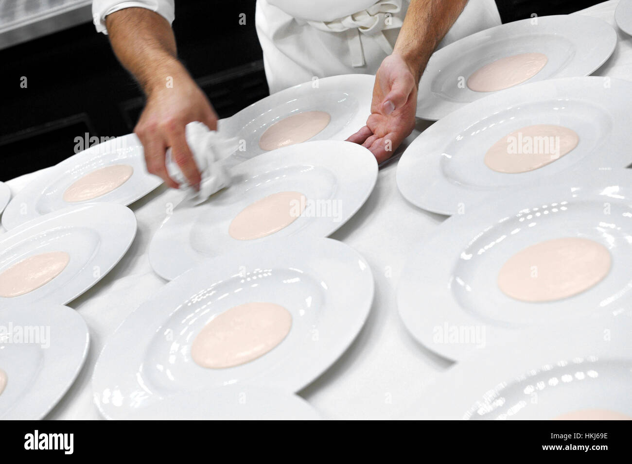 Crop view of incognito waiter in white apron holding napkin while wiping white plates with pink centre over table - Stock Image