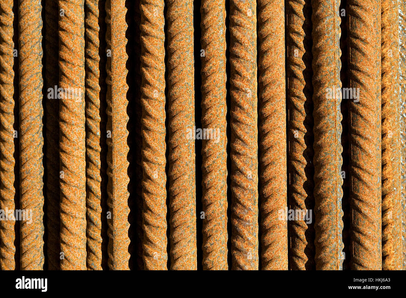 Parallel oriented rusty steel rods in sunlight background concept - Stock Image