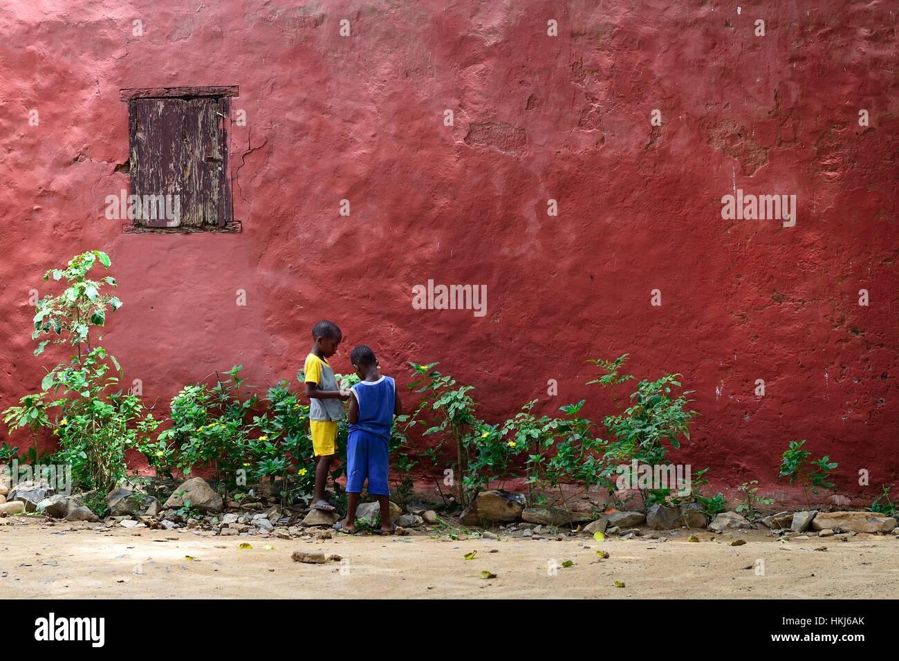 Two children in front of a red house facade, Île de Gorée, Dakar, Senegal - Stock Image