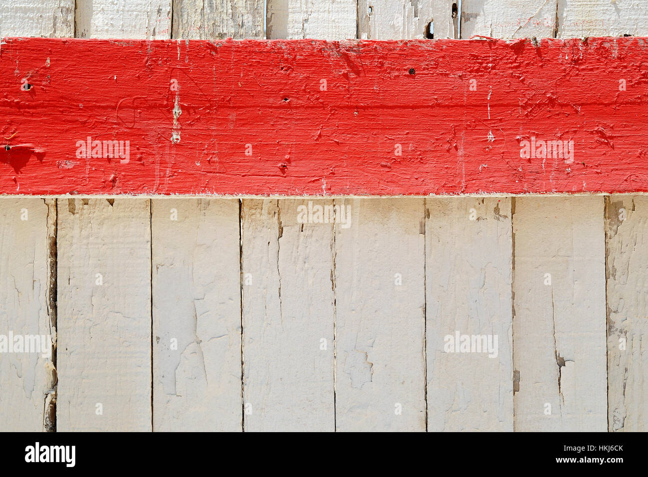 Horizontal red stripe of painted wooden board against white fence