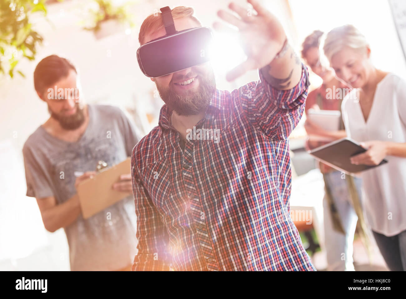 Smiling male design professional using virtual reality simulator glasses in meeting - Stock Image
