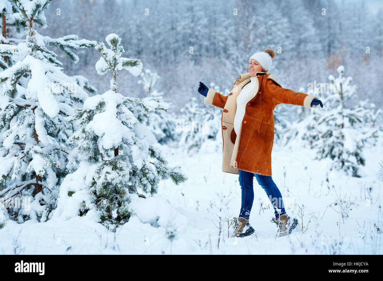 34d83e83cd Young pregnant woman wearing warm clothes having fun on winter forest