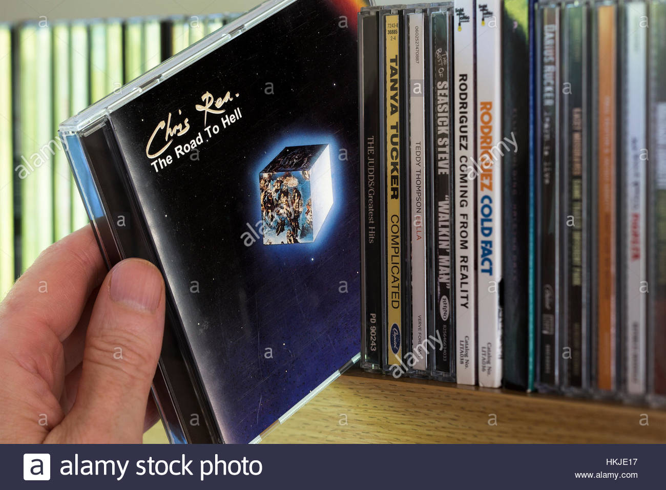 The Road To Hell, Chris Rea CD being chosen from a shelf of other CD's - Stock Image