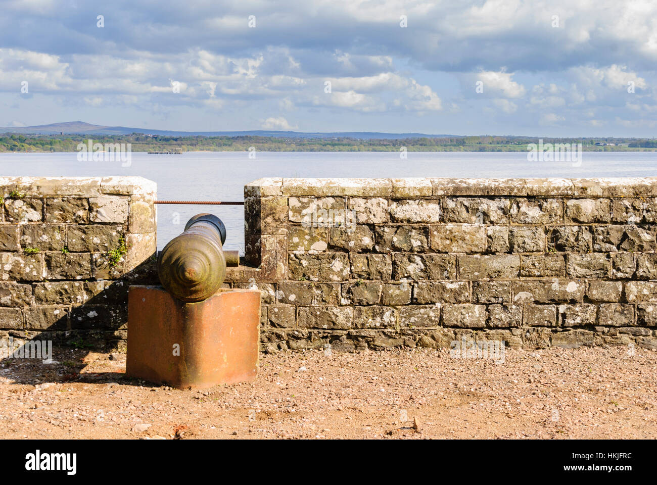 Cannon on a castle wall overlooking a narrow sea. - Stock Image