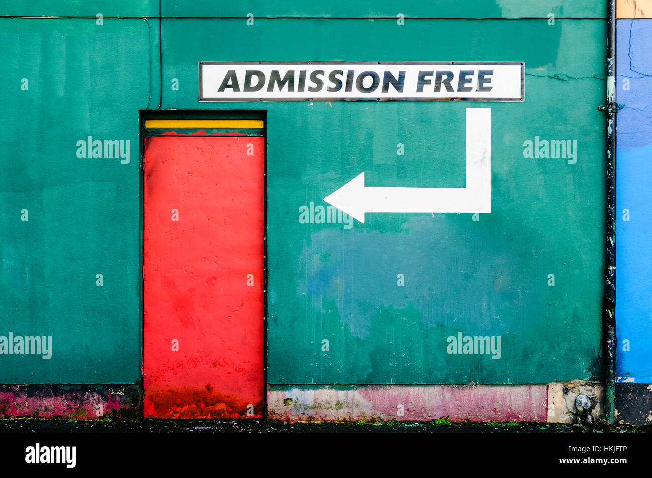 Red door on a green wall with a sign saying 'Admission Free' - Stock Image