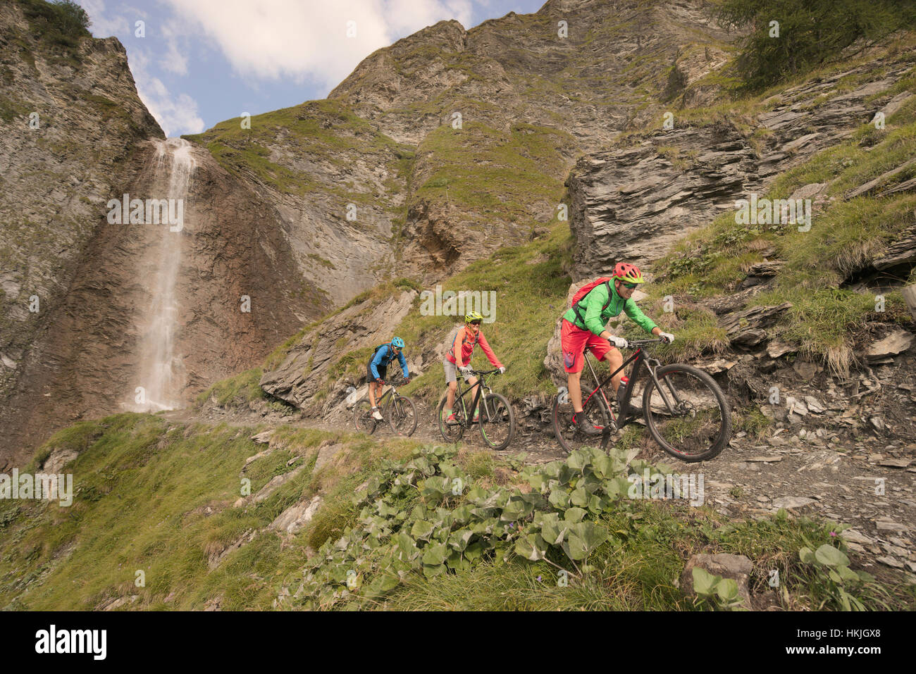 Three mountain bikers riding on hill at waterfall, Zillertal, Tyrol, Austria - Stock Image
