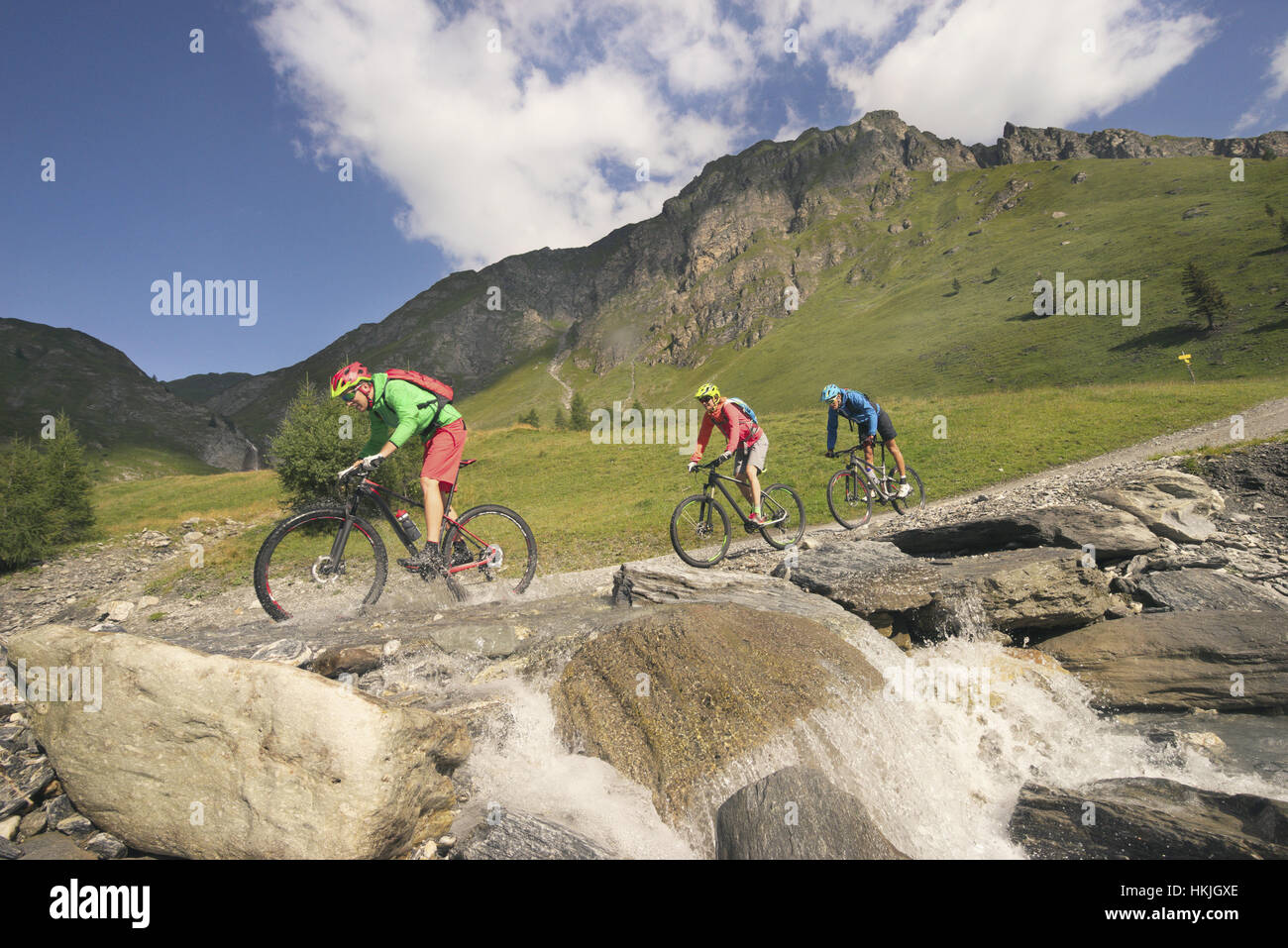 Three mountain bikers crossing stream on mountain, Zillertal, Tyrol, Austria - Stock Image