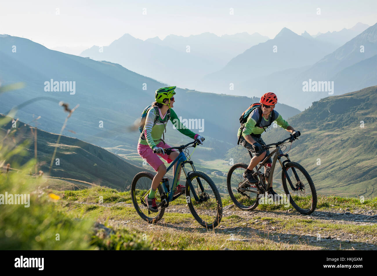 Two mountain biker friends riding on uphill, Zillertal, Tyrol, Austria - Stock Image