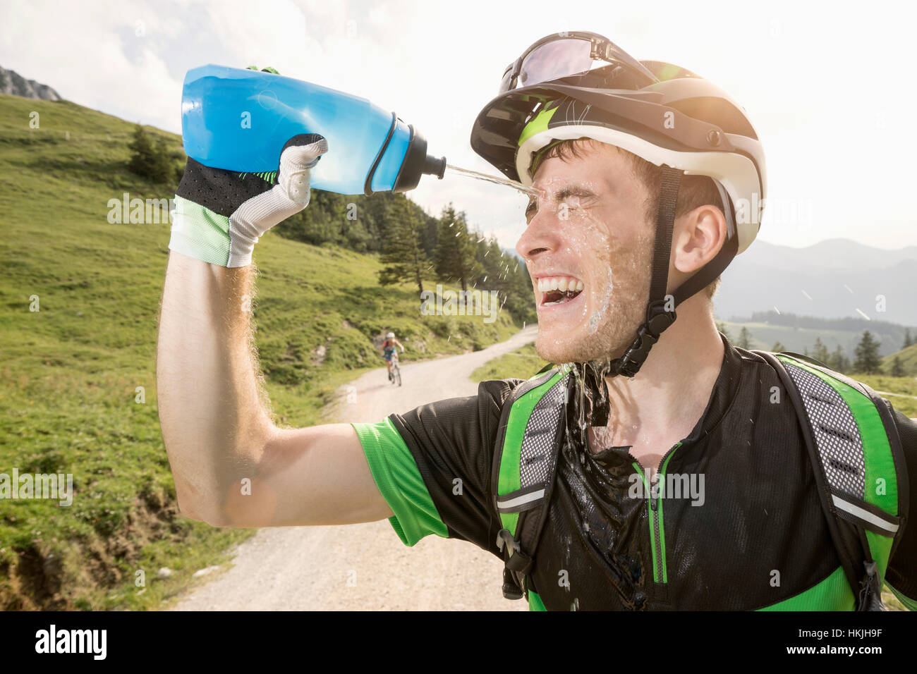Mountain biker pouring water on his face, Kampenwand, Bavaria, Germany - Stock Image