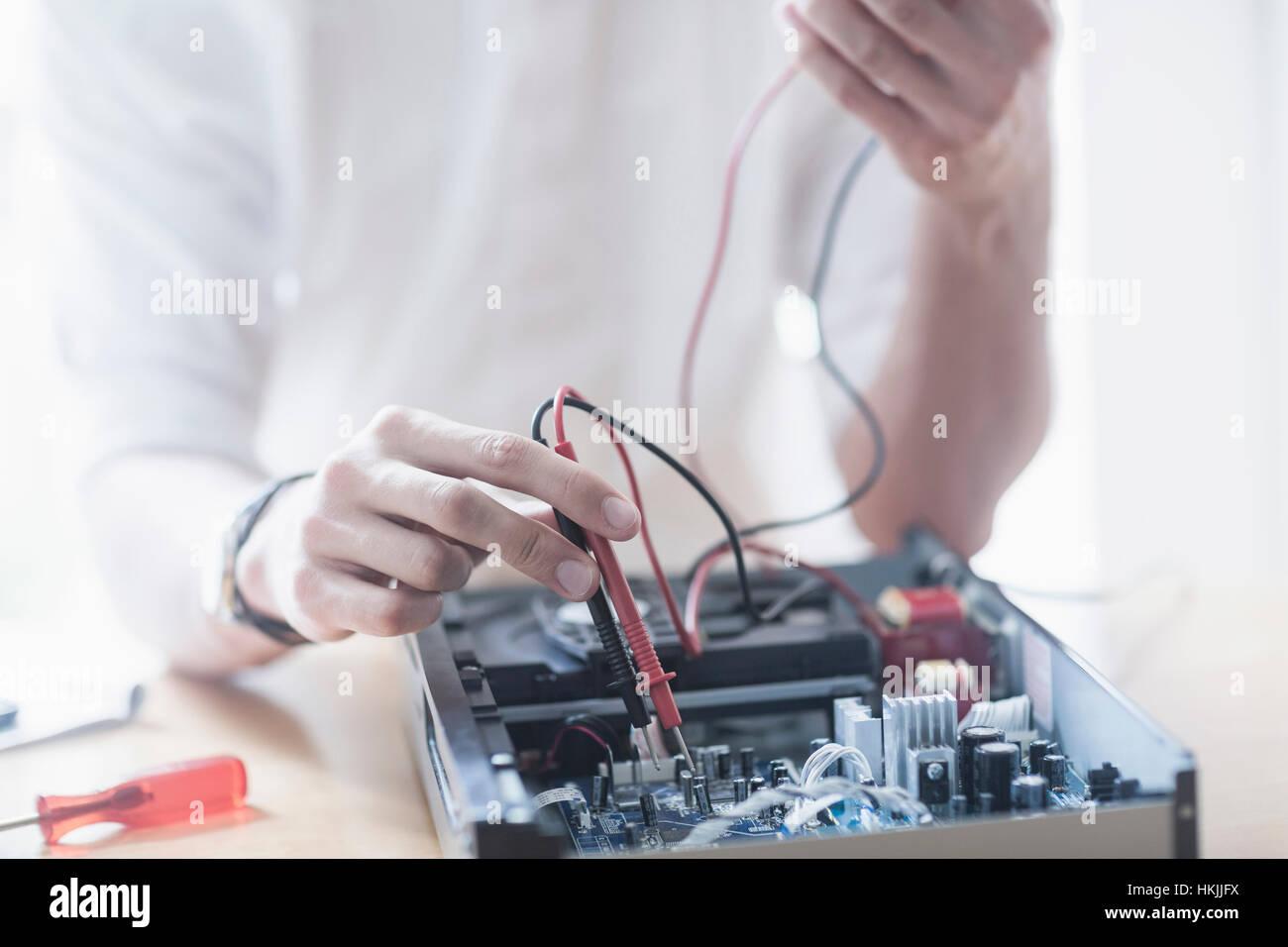 Engineer repairing CD player in workshop, Freiburg Im Breisgau, Baden-Württemberg, Germany - Stock Image