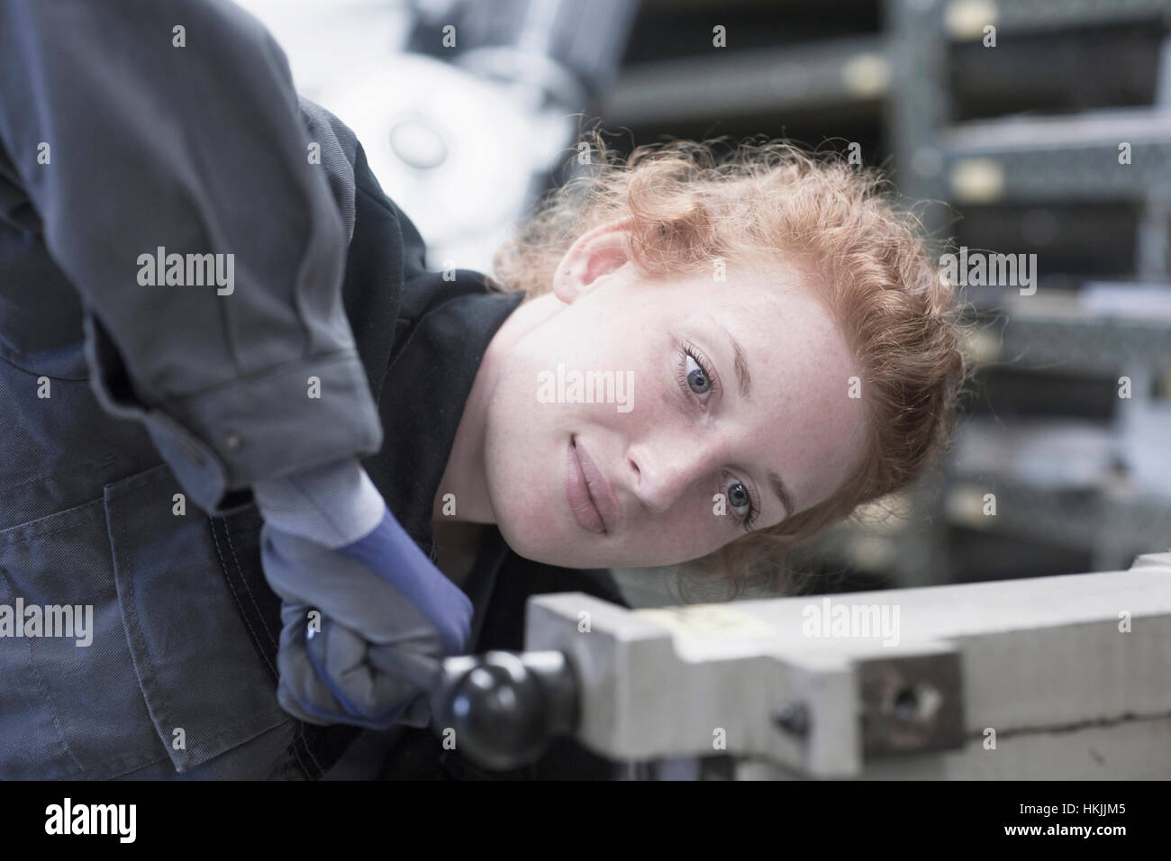 Young female engineer operating lever in an industrial plant, Freiburg im Breisgau, Baden-Württemberg, Germany - Stock Image