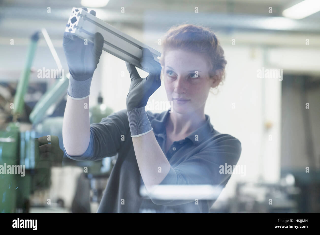 Young female engineer looking at machine part in an industrial plant, Freiburg im Breisgau, Baden-Württemberg, - Stock Image