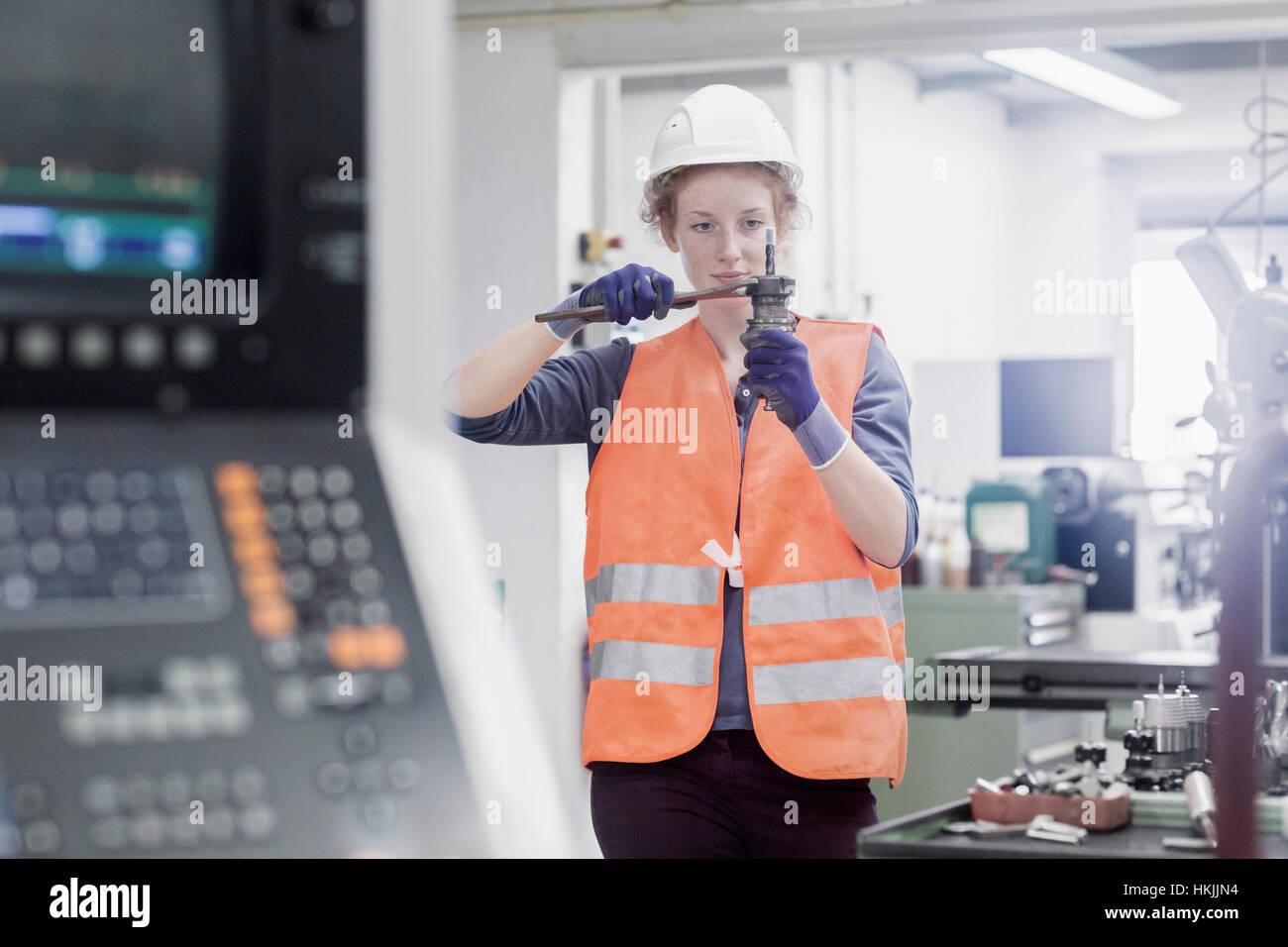 Young female engineer repairing machine part in an industrial plant, Freiburg im Breisgau, Baden-Württemberg, - Stock Image