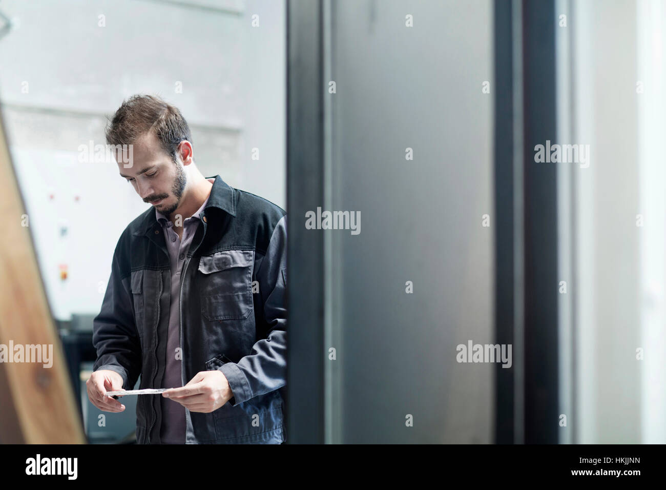 Young male engineer reading paper in technology space, Freiburg Im Breisgau, Baden-Württemberg, Germany Stock Photo