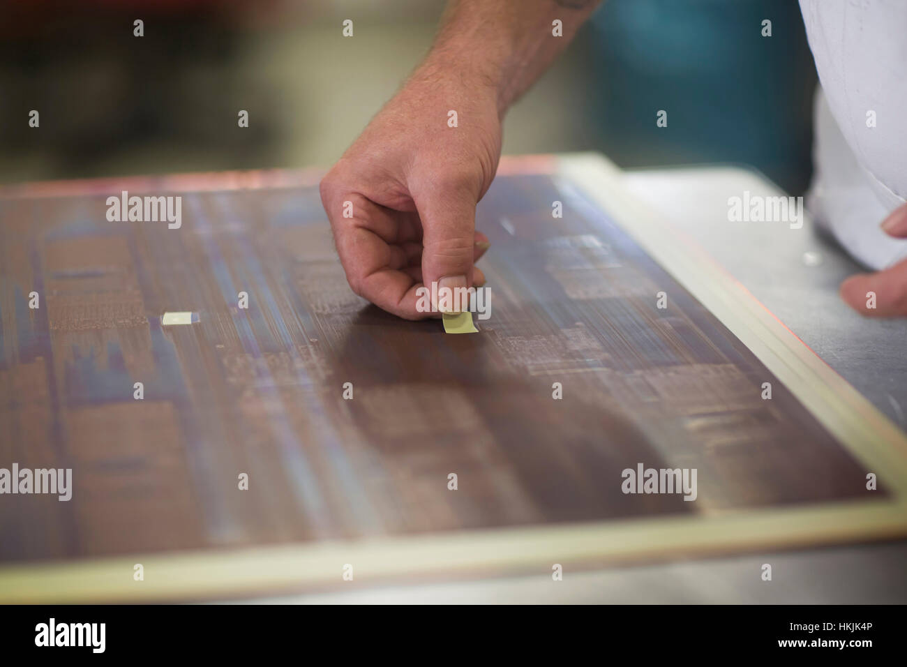 Close-up of human hand examining circuit board in industry,Hanover,Lower Saxony,Germany - Stock Image