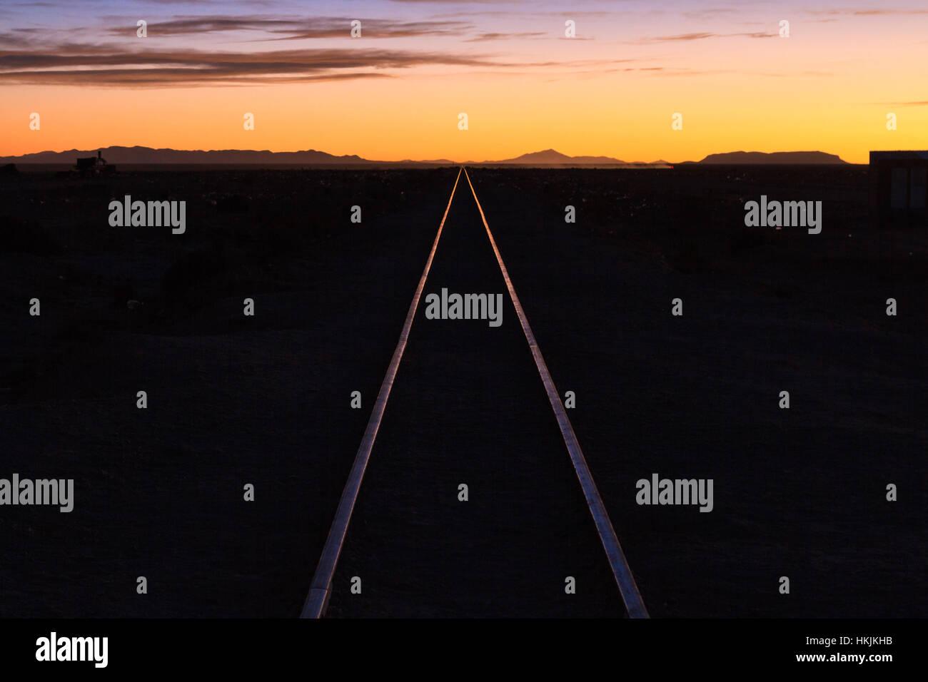 Rail track through the desert at sunset, Uyuni, Bolivia - Stock Image