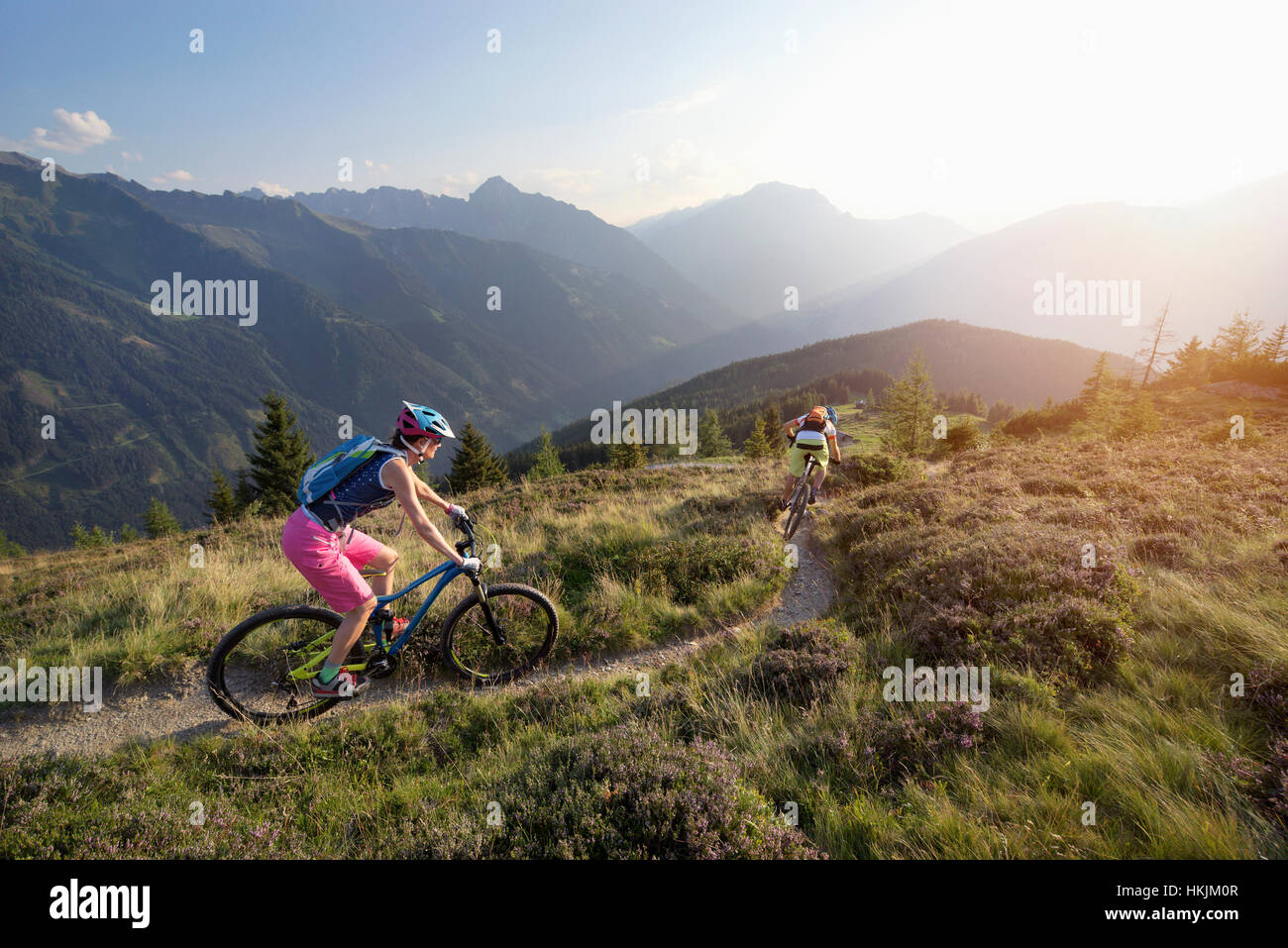 Two mountain bikers riding on hill in alpine landscape, Zillertal, Tyrol, Austria - Stock Image