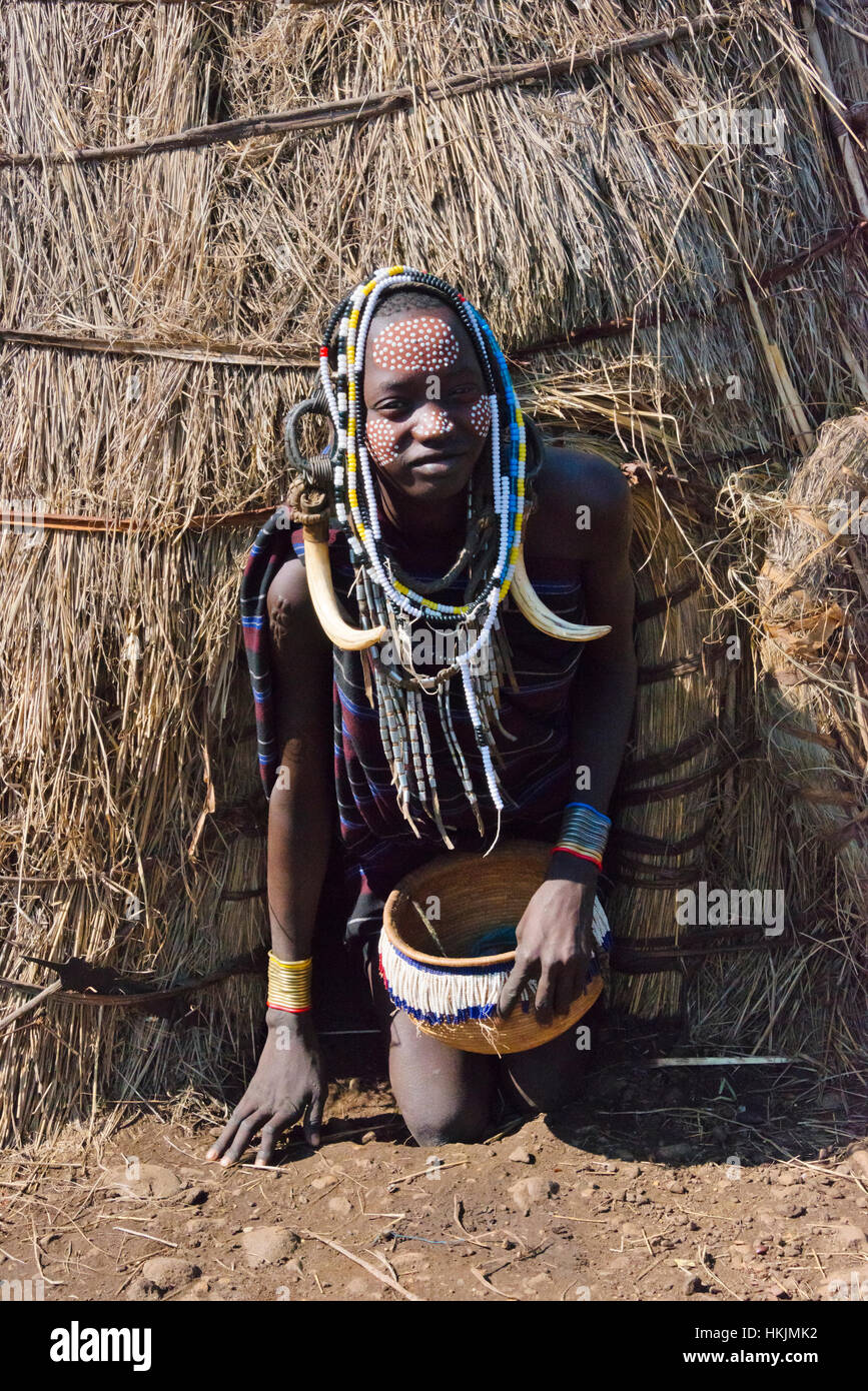Mursi tribe people in traditional clothing in front of traditional straw house, Mursi Village, South Omo, Ethiopia - Stock Image