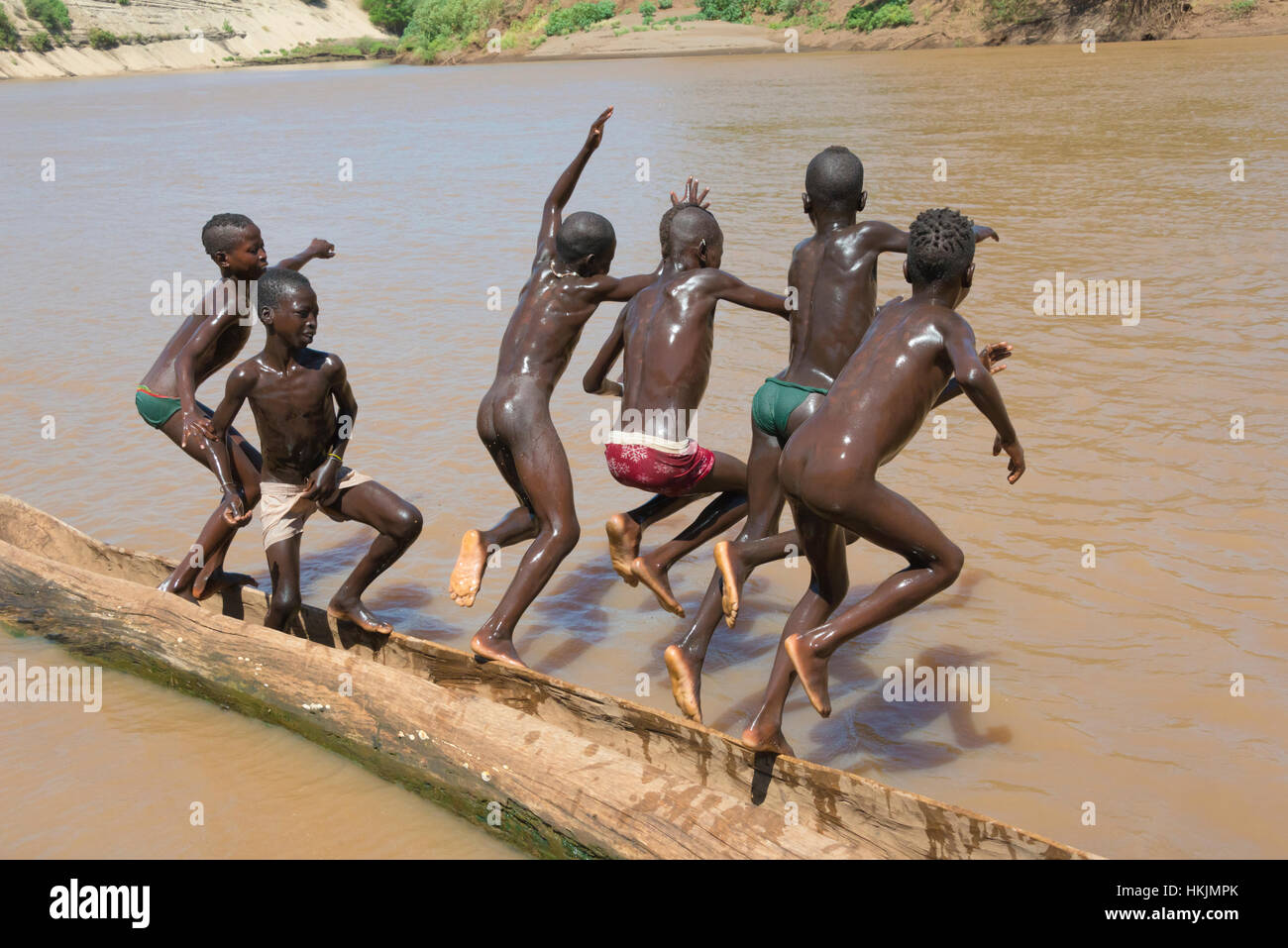 Kara tribe boys on dugout canoe on Lower Omo River, South Omo, Ethiopia - Stock Image