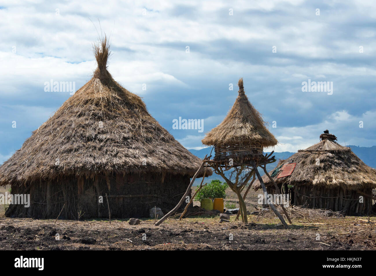 Traditional village houses with thatched roof and chicken cage in the mountain, Konso, Ethiopia - Stock Image