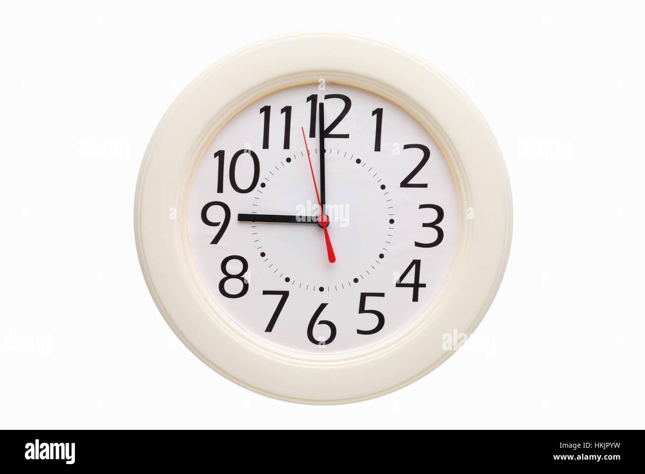 analog wall clock showing nine o'clock - Stock Image