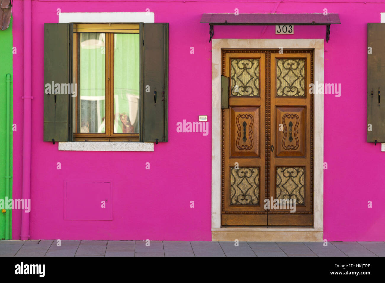 Ornate door and window shutters against bright purple pink wall of ...