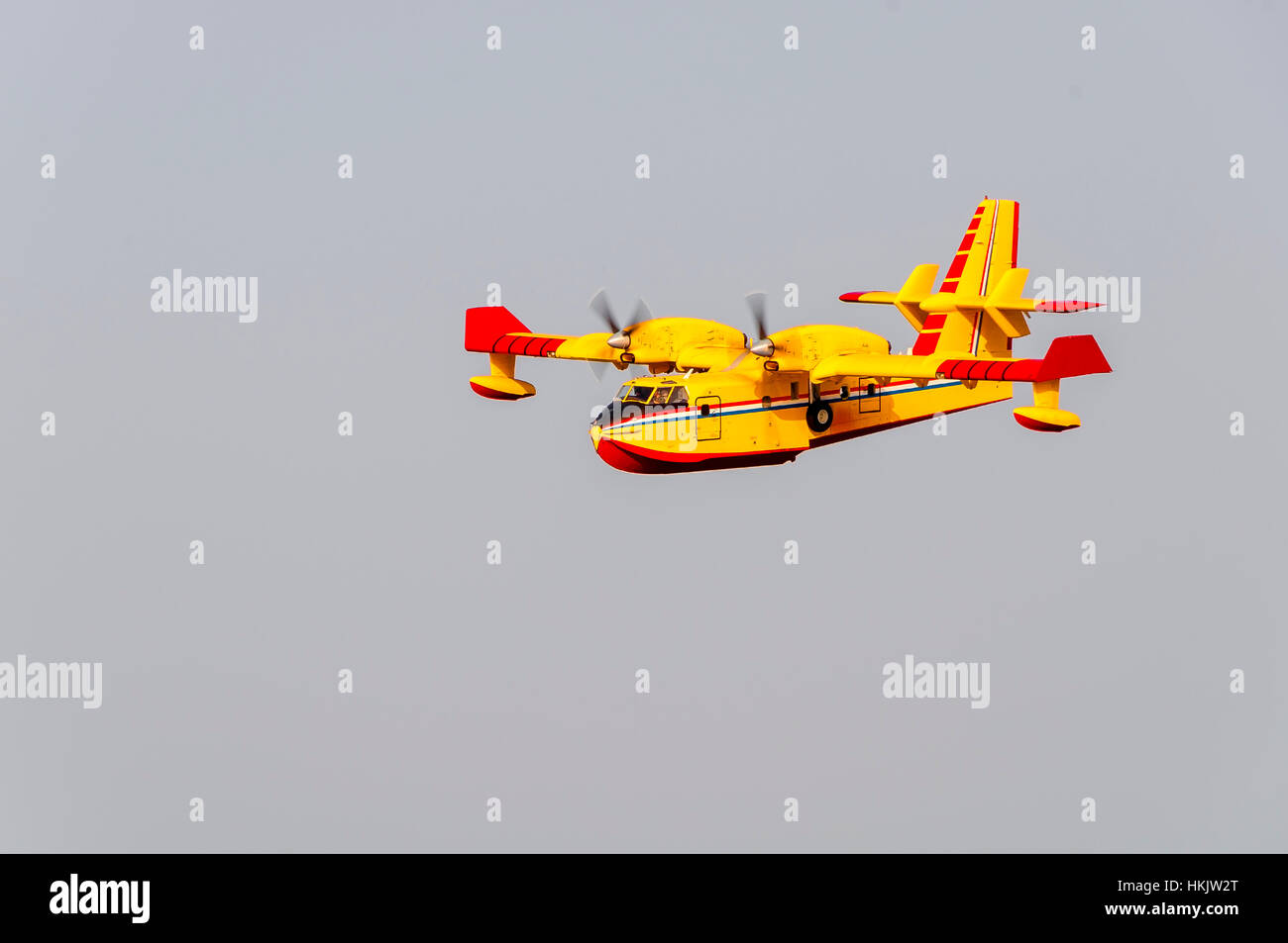 Yellow and red Canadair water bomber, turbo prop firefighting aircraft in action, banking to scoop water from sea - Stock Image