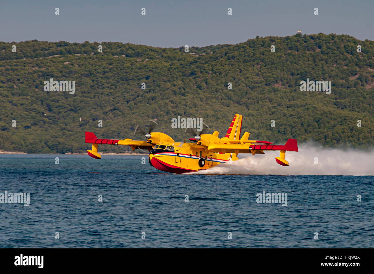 Yellow and red Canadair water bomber, turbo prop firefighting aircraft in action, scooping water - Stock Image