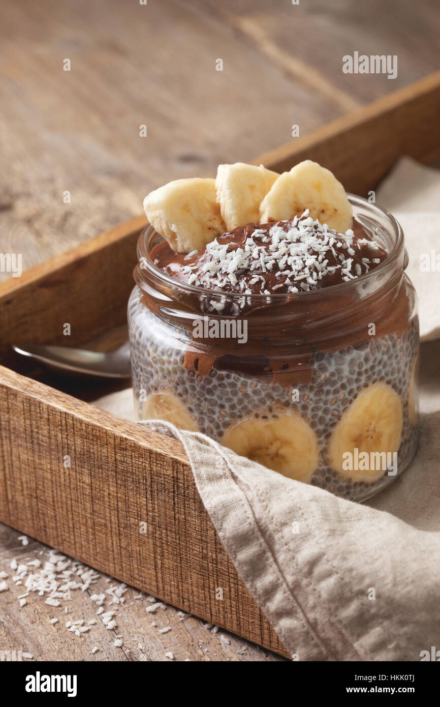 chia pudding with chocolate banana smoothie in a glass jar on the old wooden background - Stock Image