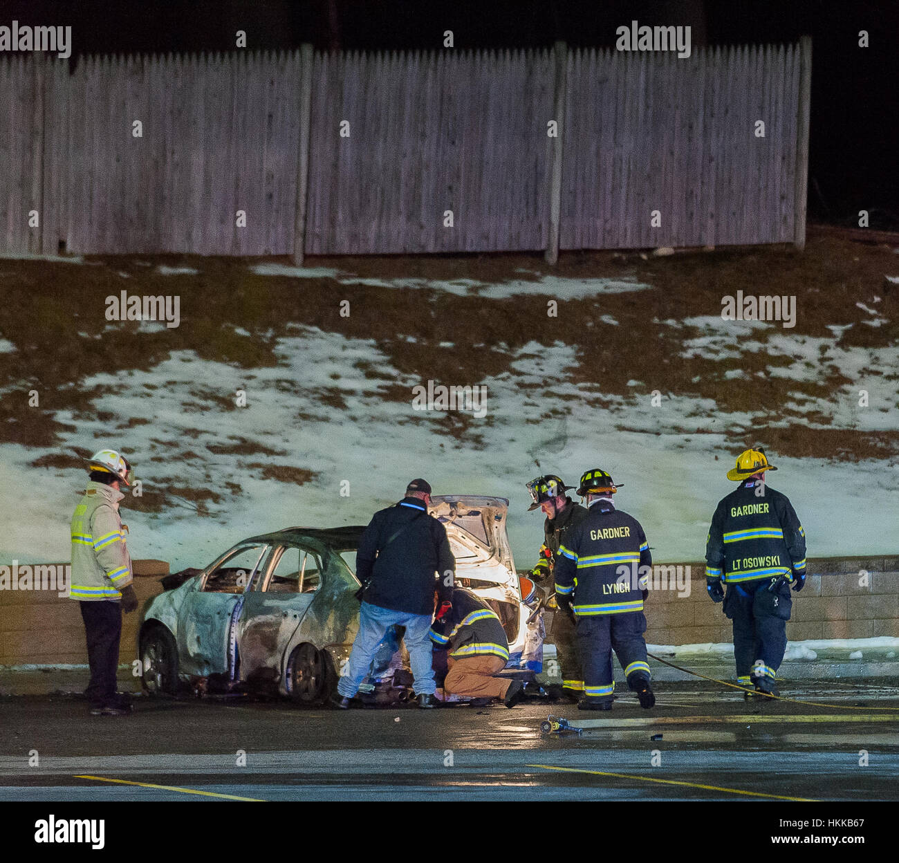 Gardner, USA. 28 January, 2017. Police and fire investigators pore over a car in the parking lot of a WalMart after - Stock Image