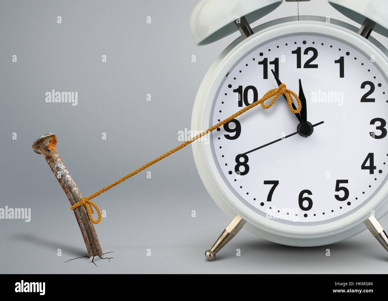Time on clock stop by nail, delay concept Stock Photo