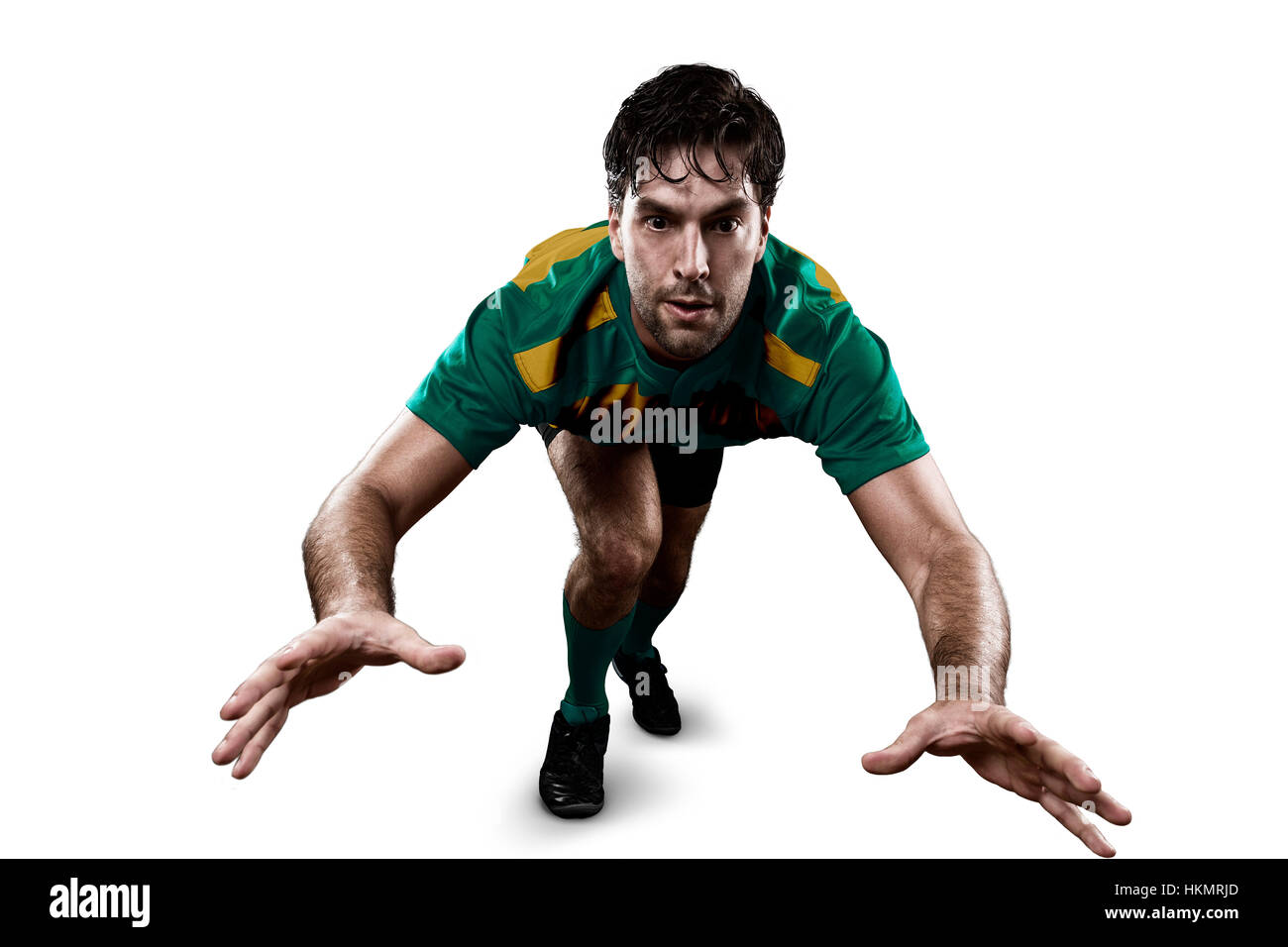 Rugby player in a green and gold uniform giving a tackle. White Background Stock Photo